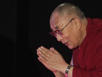 "Tibetan spiritual leader the Dalai Lama greets the audience as he arrives to speak on ""A Human Approach to World Peace"" at Presidency College in Kolkata, India, Tuesday, Jan. 13, 2015. (AP Photo/Bikas Das)"