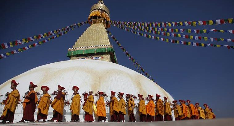 FILE- In this Nov. 20, 2016 file photo, Buddhist monks circle around the Boudhanath Stupa during during the final day of its purification ceremony in Kathmandu, Nepal. A year and a half after a colossal earthquake destroyed hundreds of its treasured historic sites, Nepal on Tuesday celebrated the restoration of the iconic Buddhist monument topped in gold that towers above Kathmandu. (AP Photo/Niranjan Shrestha, File)