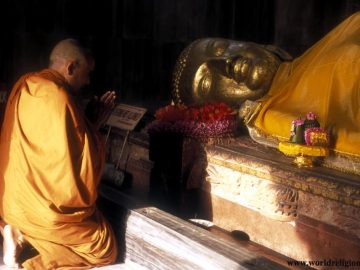Statue of the `death of Buddha` with a monk praying - parinirvana - at Kusingara India